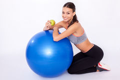 Workout snack. Portrait of a young woman sitting next to her fitness ball and eating an apple Stock Photo
