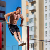 Workout, sportsman pull ups the horizontal bar with big effort Stock Photography