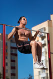 Workout, sportsman pull ups the horizontal bar with big effort Stock Images