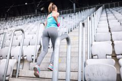 Workout at stadium, healthy female doing fitness exercises. Female running on stairs. Full body workout at stadium, healthy female doing fitness exercises Royalty Free Stock Photo