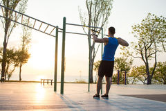 Workout with suspension straps In the outdoor gym, strong man training early in morning on the park, sunrise or sunset in the sea Stock Photos