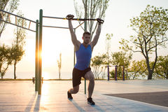 Workout with suspension straps In the outdoor gym, strong man training early in morning on the park, sunrise or sunset in the sea Royalty Free Stock Photo