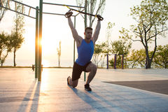 Workout with suspension straps In the outdoor gym, strong man training early in morning on the park, sunrise or sunset in the sea Stock Photo