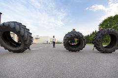 Workout team flipping heavy tires outdoor Stock Images