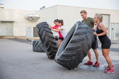 Workout team flipping tires outdoor Stock Photos