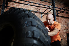 Workout with tire. Sportsman in T-shirt flipping tire in gym Stock Images