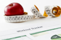 Workout tracker printout. Spreadsheet printout, red apple and measuring tape royalty free stock image
