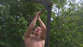 Workout training on the horizontal bar, a man doing pull-ups, training in the fresh air