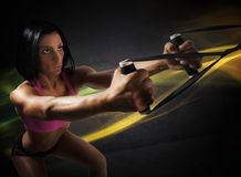 Workout with trx. Athlete girl does fitness with trx exercise Royalty Free Stock Images