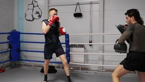 Fighters are practicing kicks using sport pads on training in fight club. Workout of two professional fighters on ringside. Fighters are practicing kicks using stock video