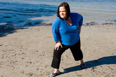 Workout at Waters Edge. Beautiful plus sized woman working out on the beach Royalty Free Stock Photography