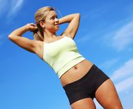 Workout Woman. Beautiful young woman in workout clothes against sky royalty free stock photography