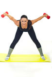 Workout woman with dumbbell. Standing on yellow mat against white background Royalty Free Stock Photos