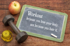 Workout because you love your body. Not because you hate it  -  fitness concept on a slate blackboard against weathered red painted barn wood with a dumbbell Stock Photos