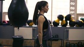 Workouter femenino moreno juguetón atractivo que hace posiciones en cuclillas, trabajando en sus glutes y caderas El conseguir li metrajes