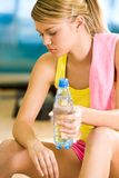 Between workouts. Photo of exerted female having a drink of water after difficult exercises Stock Images