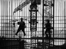 Workpeople. Construction site, evening, workers assemble the elements of the building structure Stock Images
