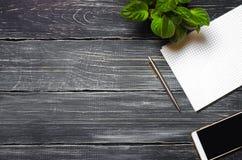 workplace над взглядом desktop телефон, тетрадь, ручка на черной деревянной предпосылке Бизнес стоковое фото rf