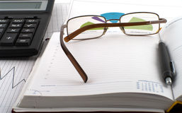 Workplace. White-collar jobs, glasses and pen on an open notebook, schedule and calculator Royalty Free Stock Photo