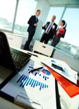 Workplace. Image of business documents on workplace with three partners on background Royalty Free Stock Photography
