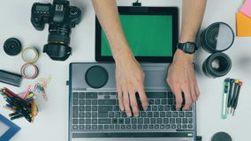 Workplace from above. Unrecognizable photographer working with his camera, tablet, memory card. Top view, greenscreen on stock video