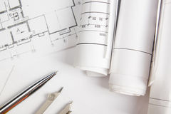 Workplace of architect - Architectural project, blueprints, rolls and pen, divider compass on plans. Engineering tools Royalty Free Stock Image