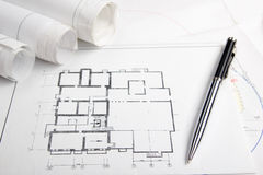 Workplace of architect - Architectural project, blueprints, rolls and tablet, pen, divider compass on plans. Engineering. Tools view from the top. Construction royalty free stock photo