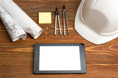 Workplace of architect - Architectural project, plan, blueprint rolls and tablet pc, pen, safety helmet on blank sheet Royalty Free Stock Photos