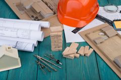 Workplace of architect - construction drawings and engineering tools, little house, model house from wooden blocks, helmet stock photography