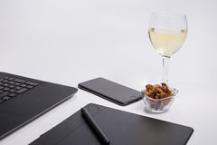 Workplace with black laptop computer, digital graphic tablet and pen, smart phone, dry grapes and glass white wine on white backgr Stock Photo
