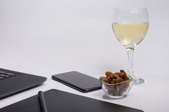 Workplace with black laptop computer, digital graphic tablet and pen, smart phone, dry grapes and glass white wine on white backgr Royalty Free Stock Photo
