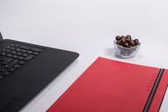 Workplace with black laptop computer, notebook and chocolate balls on white background Royalty Free Stock Photo