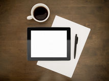 Workplace With Blank Digital Tablet. Blank digital tablet with paper, pen and cup of coffee on worktable Stock Image