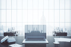 Workplace with blank laptop. Closeup of creative workplace with blank laptop computer, coffee cup, paperwork, books in office interior with city view. Mock up Royalty Free Stock Photos