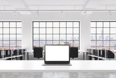 A workplace in a bright modern loft open space office. A working desk is equipped with a modern laptop with white copy space in th Stock Photography