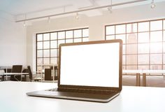 A workplace in a bright modern office. A working desk is equipped with a modern laptop with white copy space in the screen. Docs s. Helves. New York view in the Stock Image