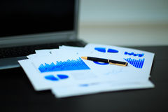 Workplace with business diagrams. Laptop, financial report in concept of business and financial stock photo