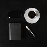 Workplace businessman. Phone, a notebook, a pen on a black table Royalty Free Stock Image