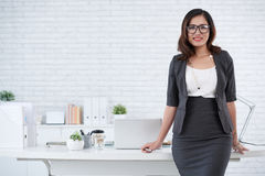 At workplace. Cheerful Asian business lady standing at her workplace royalty free stock photography