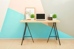 Workplace with computer in room. Near color wall Royalty Free Stock Images