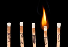 Workplace Concept. Macro of a row of matches with one on fire. Business Concept fired or A Bright Idea stock images