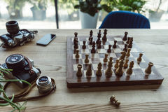 Workplace concept with old retro cameras, smartphone and chess board. Creative workplace concept with old retro cameras, smartphone and chess board Royalty Free Stock Photos