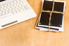 Stack of envelopes tied with rope and laptop keyboard on wooden background. stock images