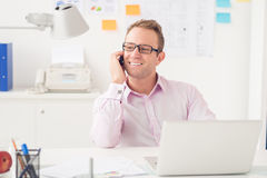 At the workplace. Copy-spaced image of a young businessman talking by phone at the workplace royalty free stock photo