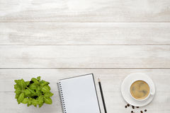 Workplace with cup of coffee, indoor plant, empty notebook and pencil on wooden surface in top view. stock photos