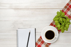 Workplace with cup of coffee, indoor plant, empty notebook and pencil on wooden surface Royalty Free Stock Image