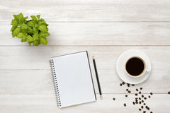 Workplace with cup of coffee, indoor plant, empty notebook and pencil on wooden surface Royalty Free Stock Photos