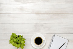 Workplace with cup of coffee, indoor plant, empty notebook and pencil on wooden surface Stock Image