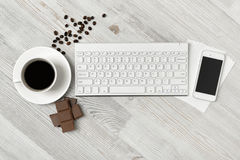 Workplace with cup of coffee, keyboard, smartphone and chocolate on wooden surface in top view. Stock Image