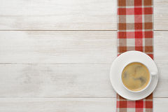 Workplace with cup of coffee and red checkered kitchen tablecloths on wooden surface in top view Stock Photography